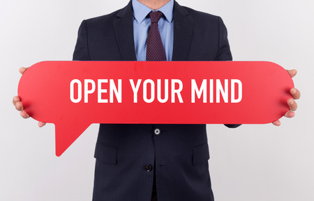 receptive: Businessman holding speech bubble with a word OPEN YOUR MIND
