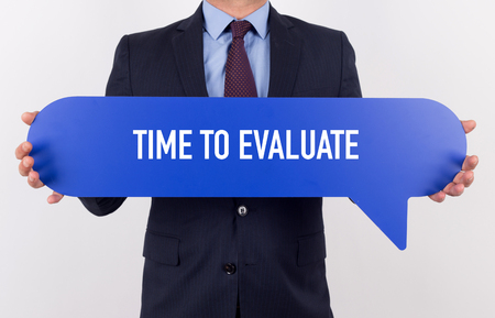 reevaluation: Businessman holding speech bubble with a word IF TIME TO EVALUATE Stock Photo