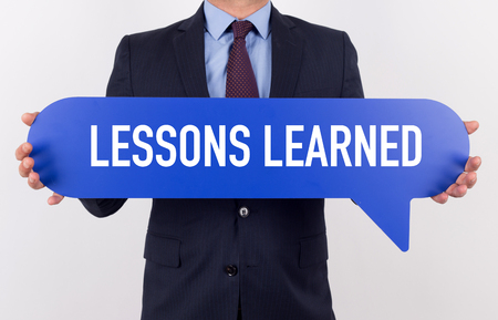 encapsulate: Businessman holding speech bubble with a word LESSONS LEARNED Stock Photo