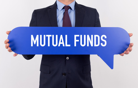 mutual: Businessman holding speech bubble with a word MUTUAL FUNDS