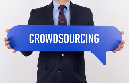 crowdsourcing: Businessman holding speech bubble with a word CROWDSOURCING