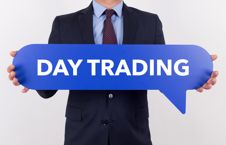 stock quotations: Businessman holding speech bubble with a word DAY TRADING
