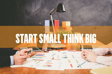 Two Businessman  Start Small Think Big working in an office
