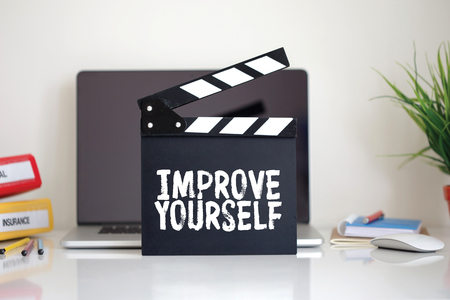 enrich: Cinema Clapper with Improve Yourself word Stock Photo
