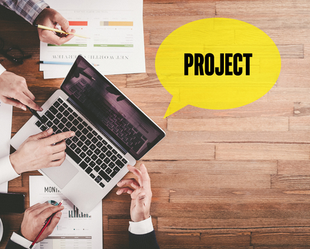businessplan: BUSINESS TEAM WORKING IN OFFICE WITH PROJECT SPEECH BUBBLE ON DESK