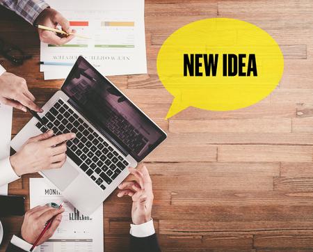 intelligent partnership: BUSINESS TEAM WORKING IN OFFICE WITH NEW IDEA SPEECH BUBBLE ON DESK