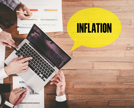 price uncertainty: BUSINESS TEAM WORKING IN OFFICE WITH INFLATION SPEECH BUBBLE ON DESK