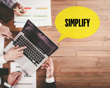 pragmatic: BUSINESS TEAM WORKING IN OFFICE WITH SIMPLIFY SPEECH BUBBLE ON DESK Stock Photo