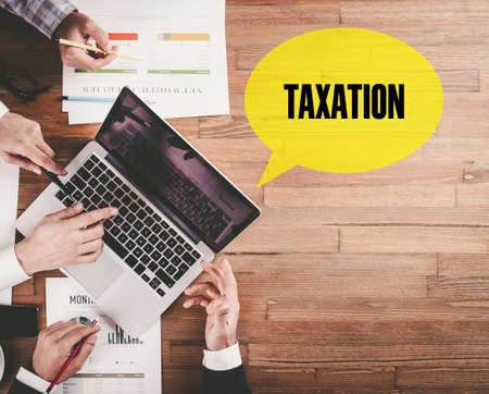 exemption: BUSINESS TEAM WORKING IN OFFICE WITH TAXATION SPEECH BUBBLE ON DESK Stock Photo