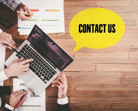 contactus: BUSINESS TEAM WORKING IN OFFICE WITH CONTACT US SPEECH BUBBLE ON DESK Stock Photo