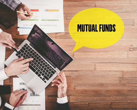 financial diversification: BUSINESS TEAM WORKING IN OFFICE WITH MUTUAL FUNDS SPEECH BUBBLE ON DESK