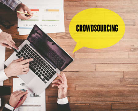 crowd source: BUSINESS TEAM WORKING IN OFFICE WITH CROWDSOURCING SPEECH BUBBLE ON DESK Stock Photo