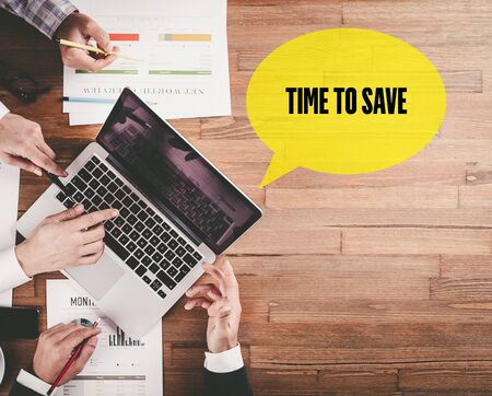 frugality: BUSINESS TEAM WORKING IN OFFICE WITH TIME TO SAVE SPEECH BUBBLE ON DESK