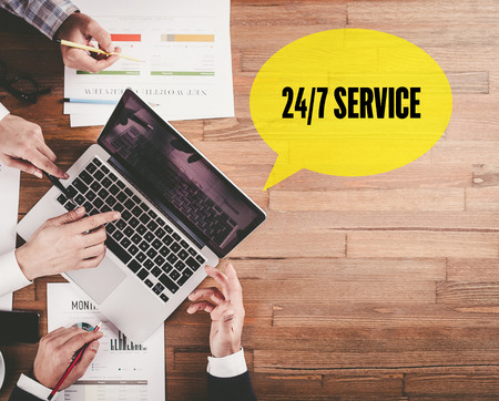 24x7: BUSINESS TEAM WORKING IN OFFICE WITH 247 SERVICE SPEECH BUBBLE ON DESK