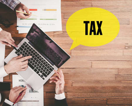 financial concept: BUSINESS TEAM WORKING IN OFFICE WITH TAX SPEECH BUBBLE ON DESK