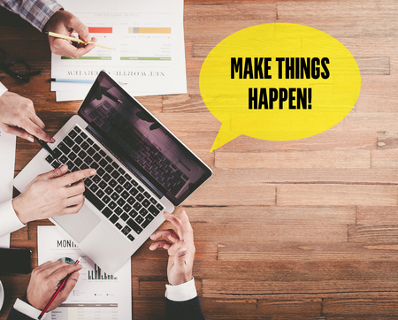 BUSINESS TEAM WORKING IN OFFICE WITH MAKE THINGS HAPPEN! SPEECH BUBBLE ON DESK Stock Photo
