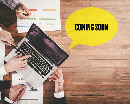 presently: BUSINESS TEAM WORKING IN OFFICE WITH COMING SOON SPEECH BUBBLE ON DESK Stock Photo