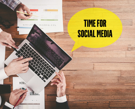 BUSINESS TEAM WORKING IN OFFICE WITH TIME FOR SOCIAL MEDIA SPEECH BUBBLE ON DESK Stock Photo