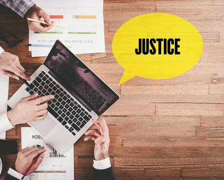 judicature: BUSINESS TEAM WORKING IN OFFICE WITH JUSTICE SPEECH BUBBLE ON DESK Stock Photo