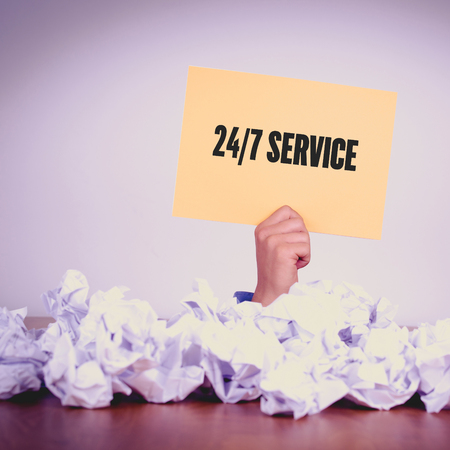 24x7: HAND HOLDING YELLOW PAPER WITH 247 SERVICECONCEPT Stock Photo