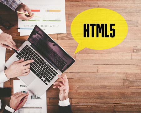html5: BUSINESS TEAM WORKING IN OFFICE WITH HTML5 SPEECH BUBBLE ON DESK Stock Photo
