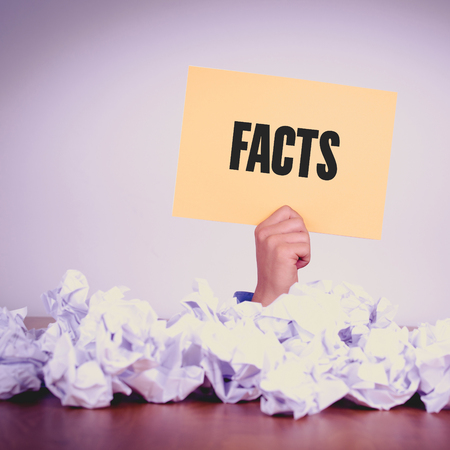 factual: HAND HOLDING YELLOW PAPER WITH FACTSCONCEPT