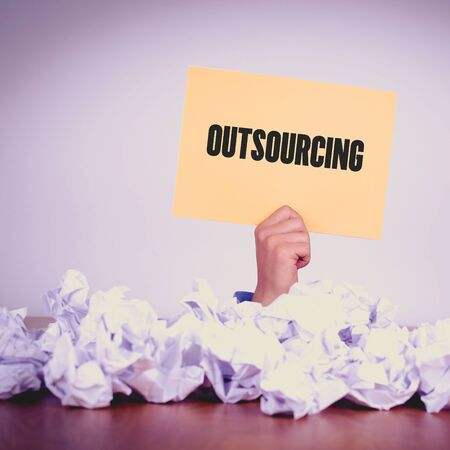 offshoring: HAND HOLDING YELLOW PAPER WITH OUTSOURCINGCONCEPT Stock Photo