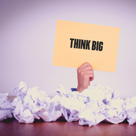 overachieving: HAND HOLDING YELLOW PAPER WITH THINK BIGCONCEPT Stock Photo