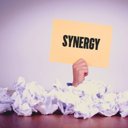 relate: HAND HOLDING YELLOW PAPER WITH SYNERGYCONCEPT