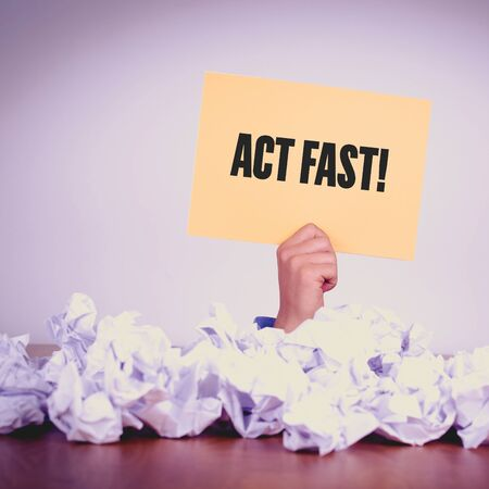 expiring: HAND HOLDING YELLOW PAPER WITH ACT FAST!CONCEPT Stock Photo