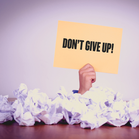 commitment committed: HAND HOLDING YELLOW PAPER WITH DONT GIVE UP!CONCEPT Stock Photo