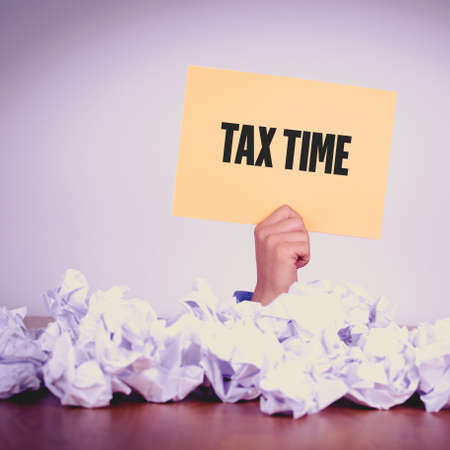 exemption: HAND HOLDING YELLOW PAPER WITH TAX TIMECONCEPT