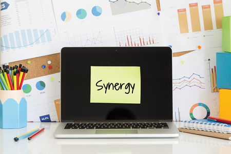 partake: SYNERGY sticky note pasted on the laptop screen Stock Photo