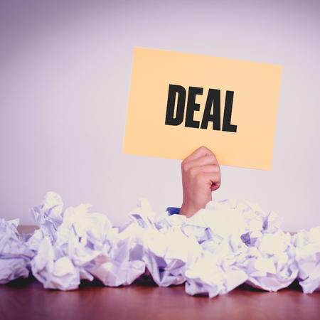 businessmeeting: HAND HOLDING YELLOW PAPER WITH DEALCONCEPT