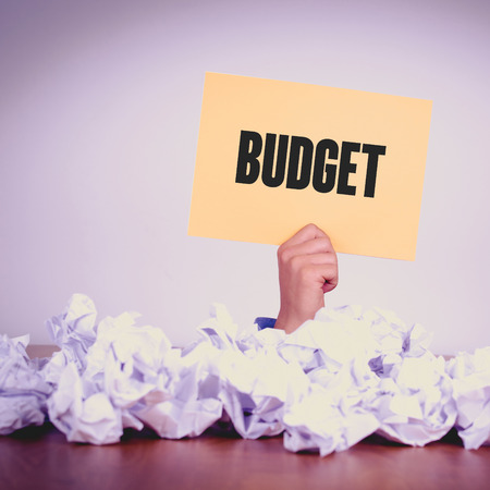 deficit target: HAND HOLDING YELLOW PAPER WITH BUDGETCONCEPT Stock Photo