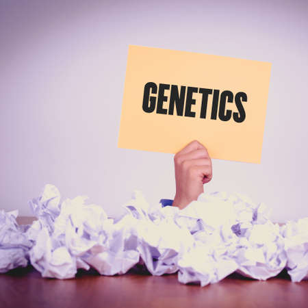 genomes: HAND HOLDING YELLOW PAPER WITH GENETICSCONCEPT