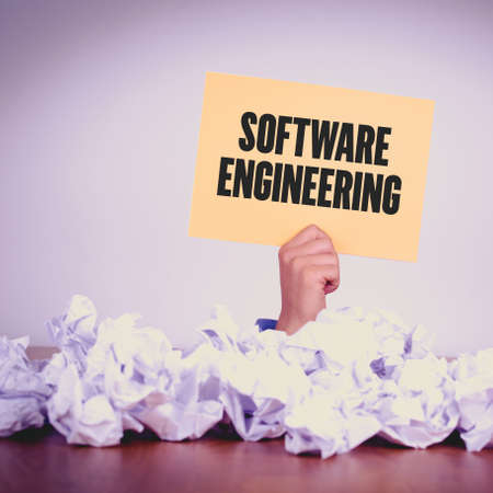 programmers: HAND HOLDING YELLOW PAPER WITH SOFTWARE ENGINEERINGCONCEPT