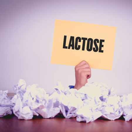 lactose intolerant: HAND HOLDING YELLOW PAPER WITH LACTOSECONCEPT