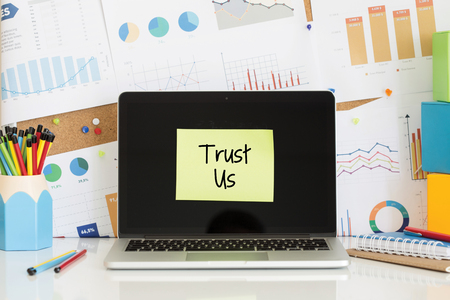 trustworthiness: TRUST US sticky note pasted on the laptop screen Stock Photo