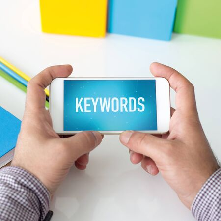 keywords: Man holding smartphone which displaying Keywords Stock Photo