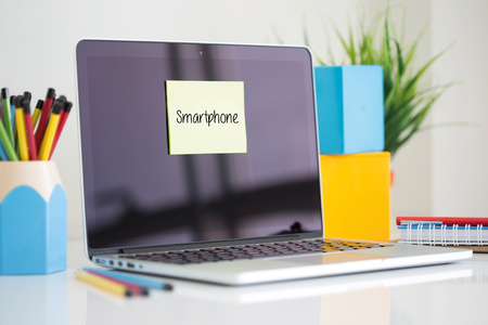 sticky note: Smartphone sticky note pasted on the laptop Stock Photo