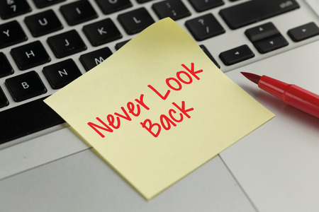 forthcoming: Never Look Back sticky note pasted on the keyboard