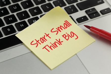 surpass: Start Small Think Big sticky note pasted on the keyboard
