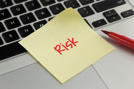 sticky note: Risk sticky note pasted on the keyboard Stock Photo