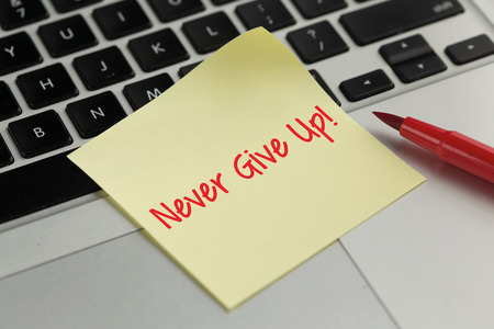 commitment committed: Never Give Up! sticky note pasted on the keyboard Stock Photo