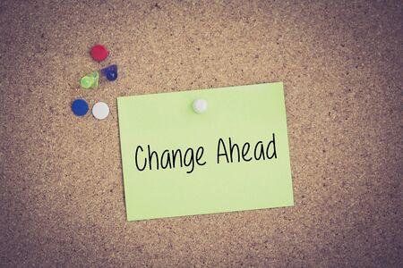 Change Ahead written on sticky note pinned on pinboard