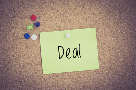 businessmeeting: Deal written on sticky note pinned on pinboard