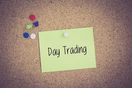 stock quotations: Day Trading written on sticky note pinned on pinboard
