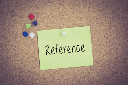 reference: Reference written on sticky note pinned on pinboard Stock Photo