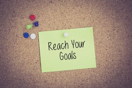 reach: Reach Your Goals written on sticky note pinned on pinboard